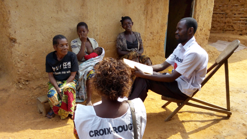 Two Congolese Red Cross workers - one male, one female - talk to three local women, one of whom is breastfeeding a baby.