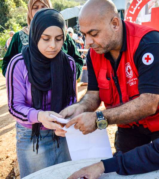 A male Red Cross worker helps a muslim woman with some paperwork at a camp. Another muslim woman waits in line behind her.
