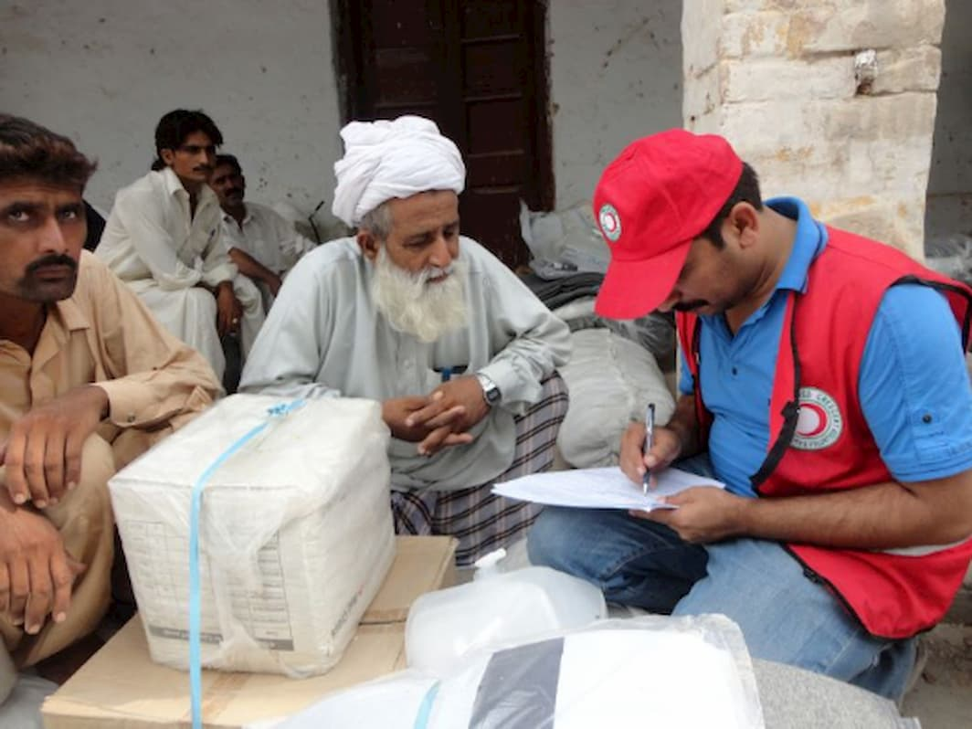 A Pakistani elder wearing a turban receives a relief package from a Red Cross worker who is filling out a form