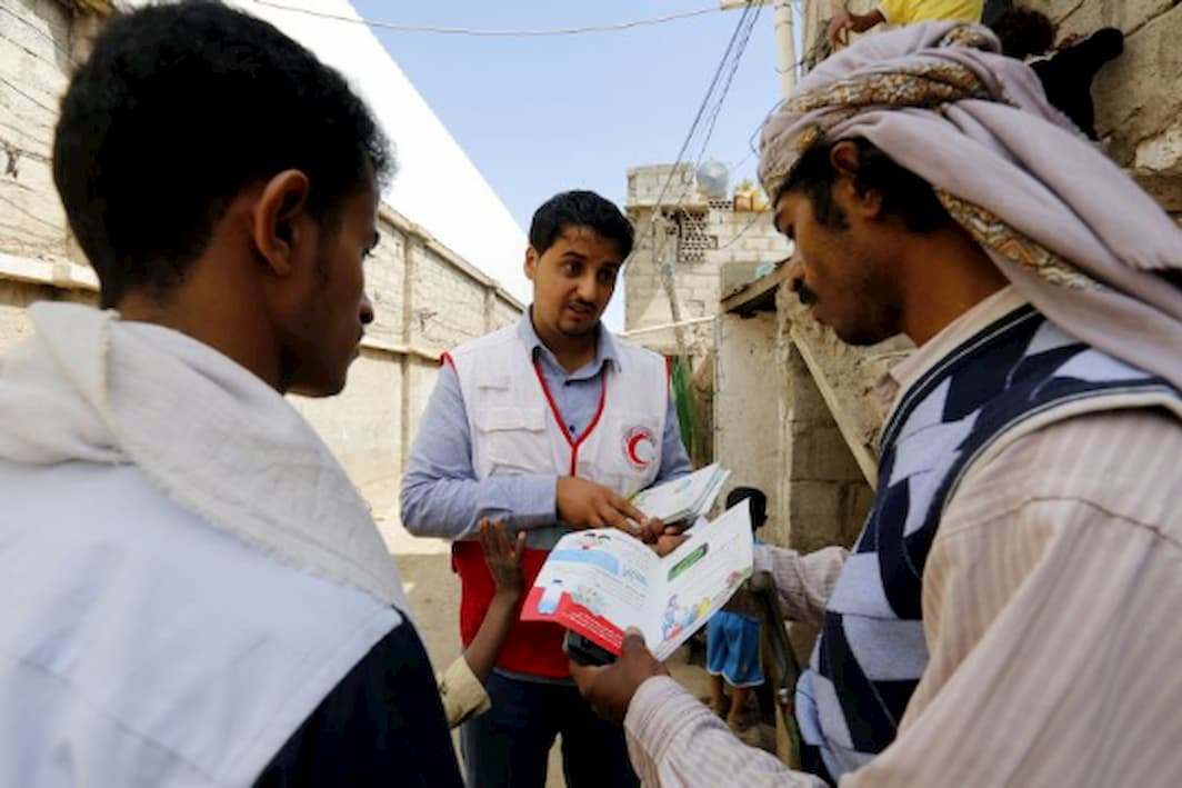 A Red Cross volunteer worker distributes leaflets about cholera to two men on the street.