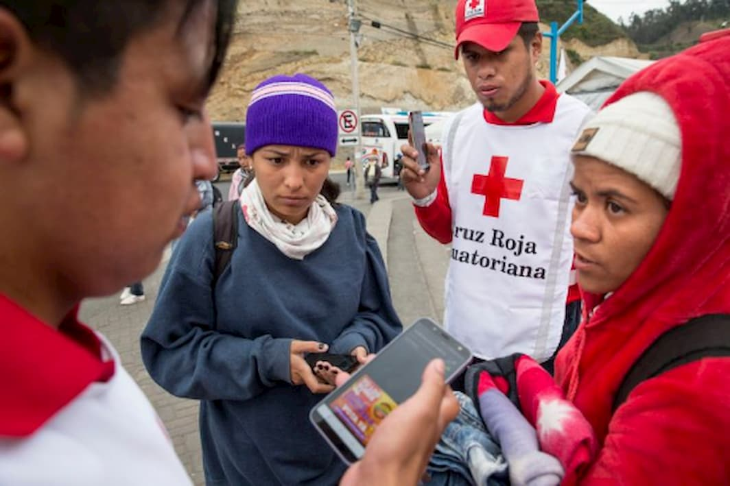 Red Cross volunteers help Ecuadorian migrants to contact their families by offering a free call service with smartphones
