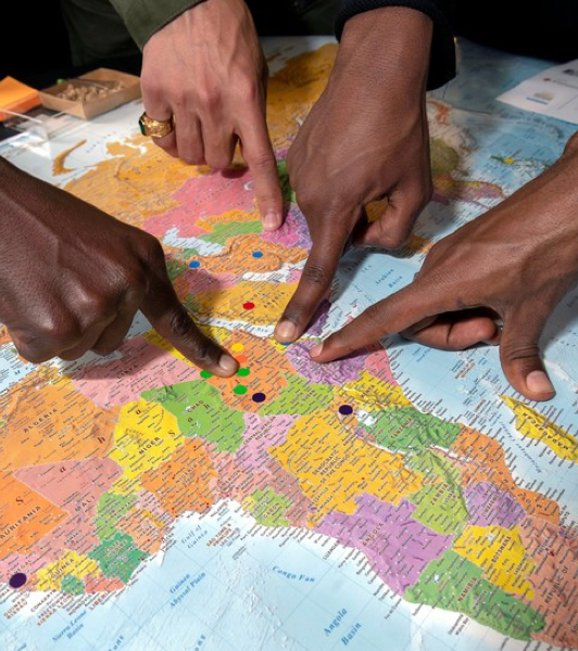 Four hands of different people pointing at a map of the world