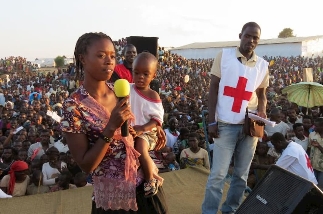 A woman holding a baby speaks into a microphone on stage whilst Red Cross workers and a large crowd watches behind her